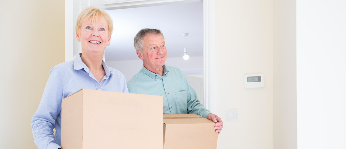 Happy senior couple holding moving boxes.
