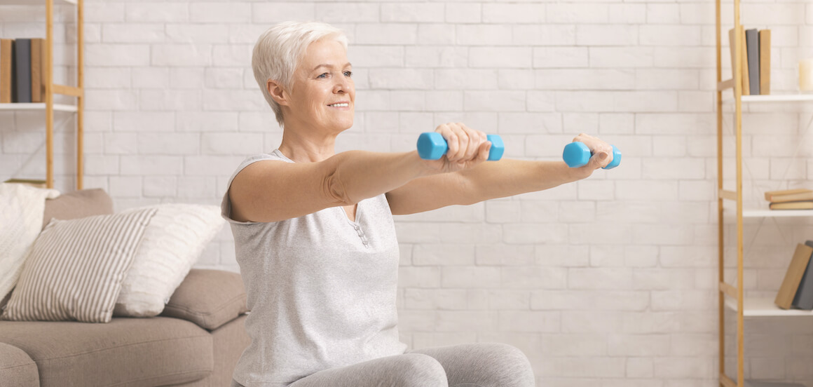 Happy senior woman works out in her living room.