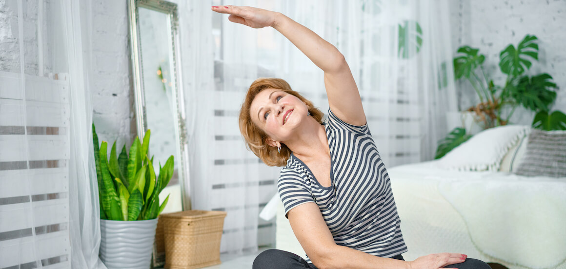 Senior woman practices yoga in the comfort of her living room.