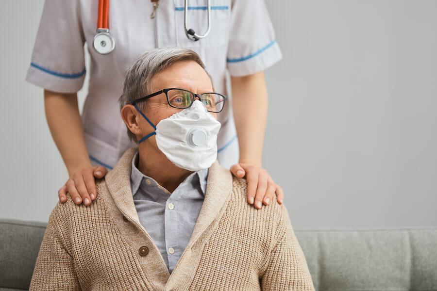 Senior man wears a mask while visting with his doctor.