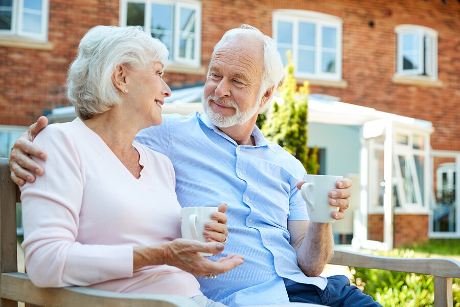Happy senior couple enjoys coffee outside at their assisted living community.
