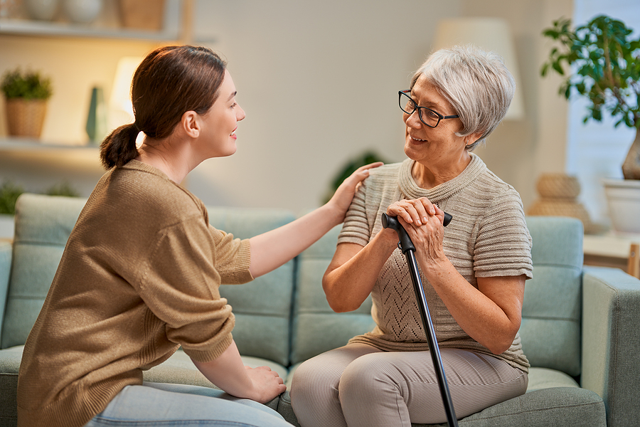 Senior woman with dementia visiting with her adult caregiver.