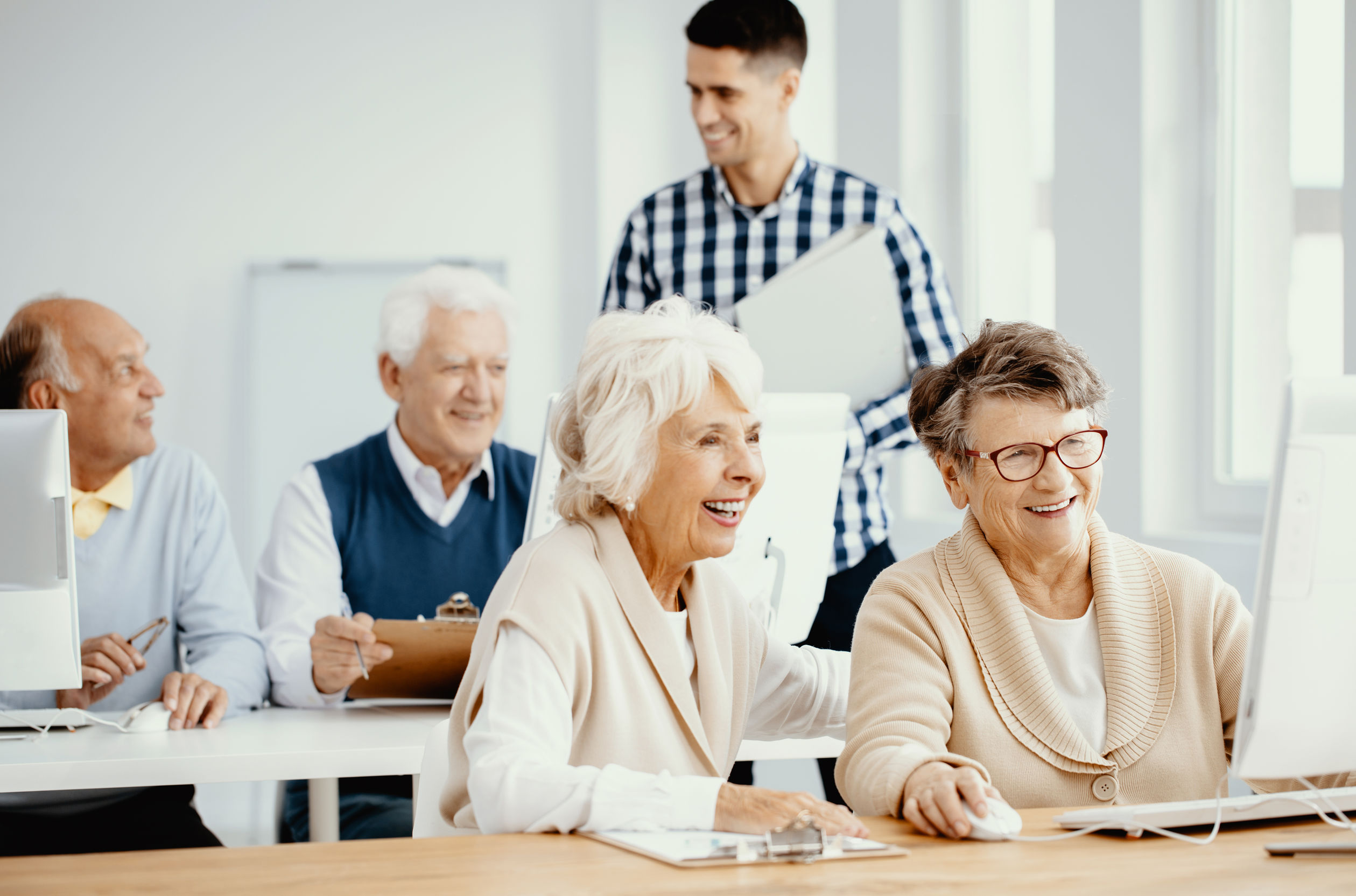 group of active seniors learning how to use computers