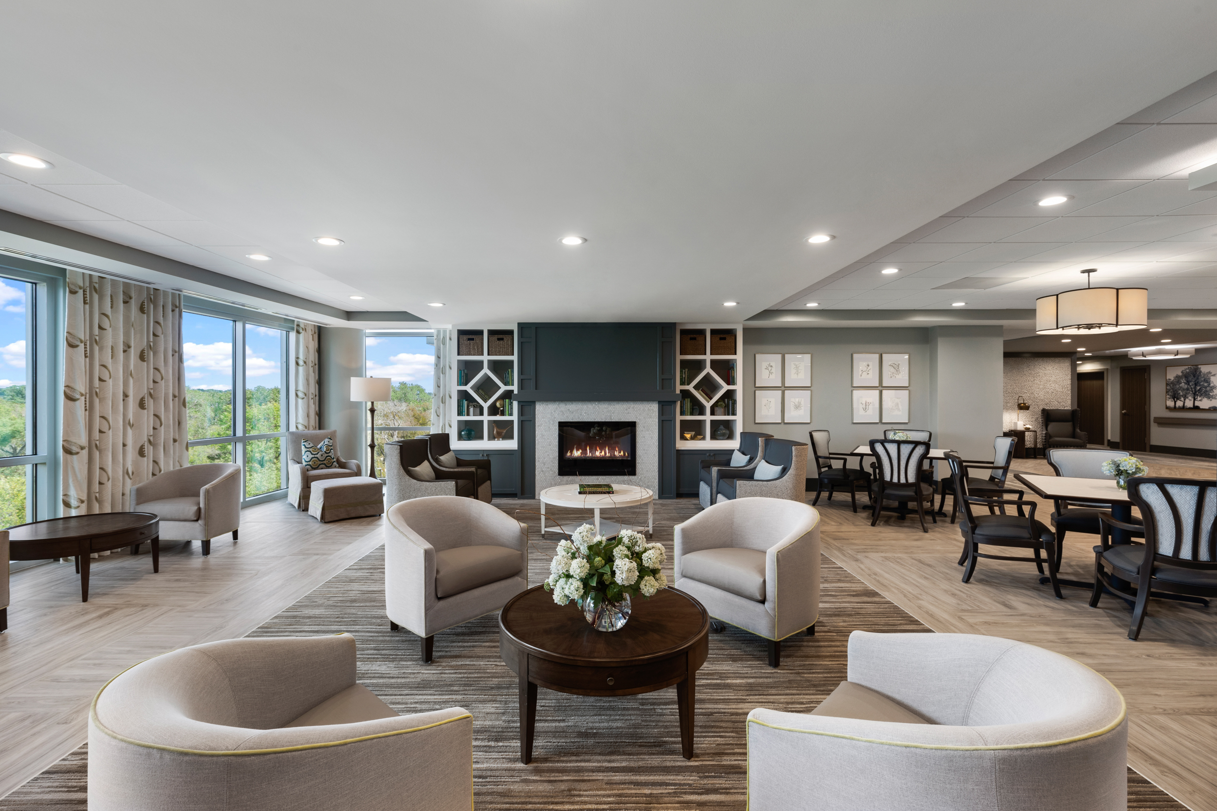 common area inside the vista featuring chairs, tables, and a fireplace