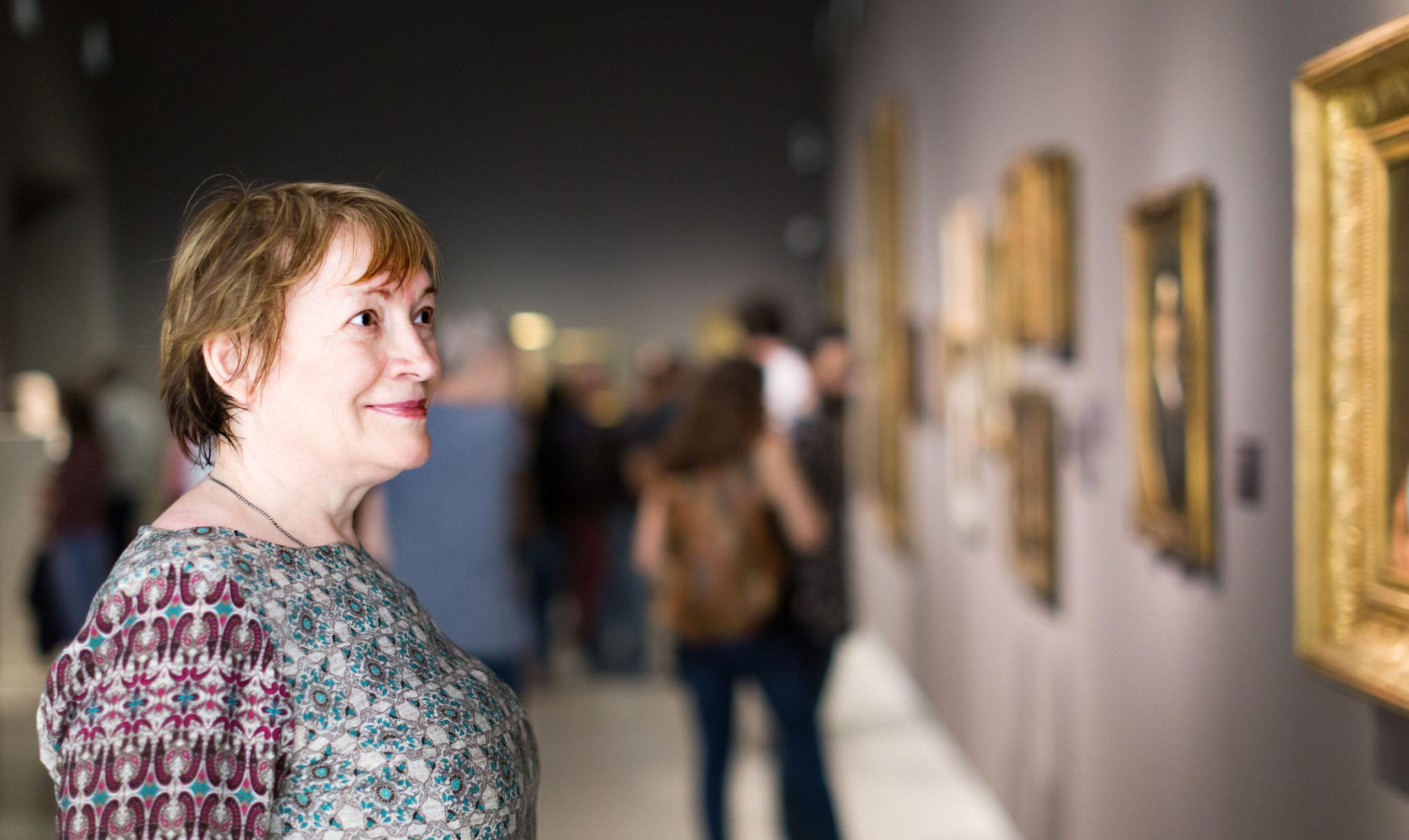 senior woman looking at hanging artwork