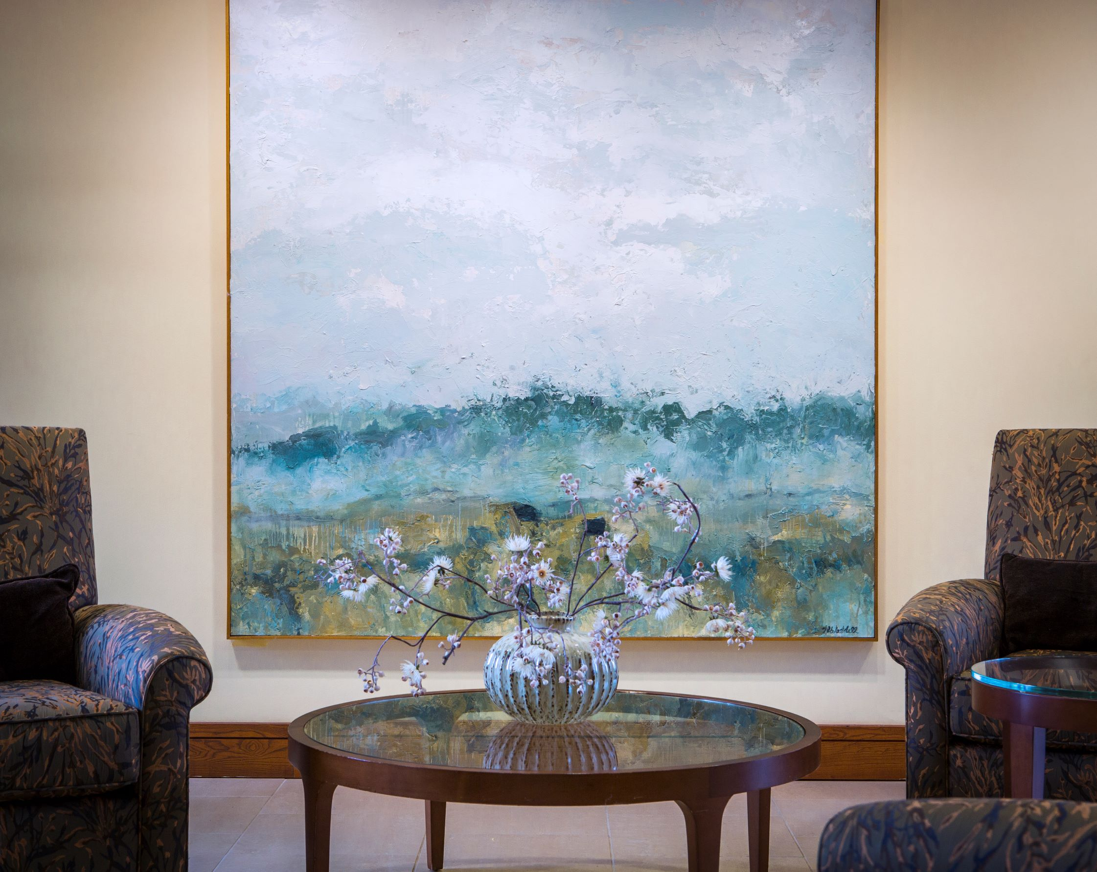 artwork hanging on the wall with two chairs